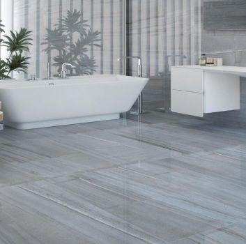 Szara łazienka z wanną wolnostojącą, białymi szafkami z wbudowaną umywalką oraz drewnianymi stoliczkami