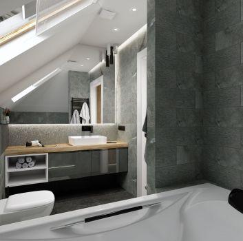 Szara łazienka z zabudowaną płytkami wanną, toaletą oraz szarą szafką z umywalką nablatową