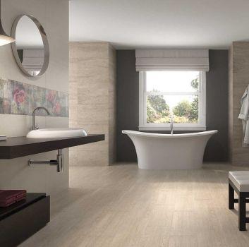 Beżowa łazienka z wanną wolnostojącą, drewnianym blatem na którym jest umywalka i małym siedziskiem pod ścianą
