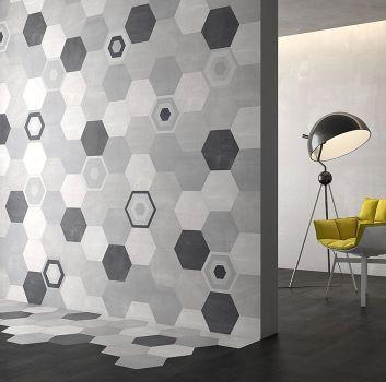 Szary pokój z limonkowym fotelem oraz czarną lampą oraz przejściem do pokoju w którym jest ściana z płytkami heksagonalnymi