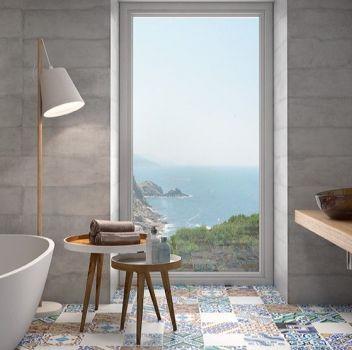 Multikolorowa łazienka z wanną wolnostojącą, dużym oknem i drewnianym blatem z dwoma umywalkami nablatowymi