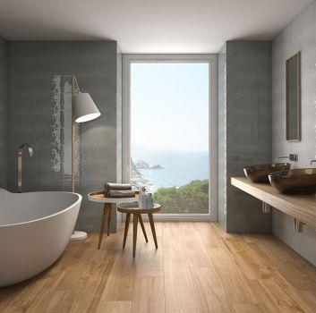 Szara łazienka z wanną wolnostojącą, dwoma umywalkami nablatowymi oraz dużym oknem