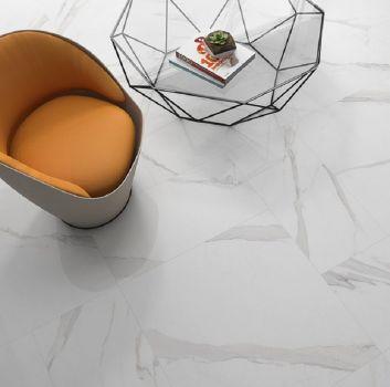 Biały salon z pomarańczowym fotelem i geometrycznym, czarnym stolikiem