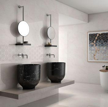 Beżowa lazienka z okrągłą wanną wolnostojącą, blatem na którym stoją dwie nablatowe umywalki a nad nimi wiszą lustra z półeczkami