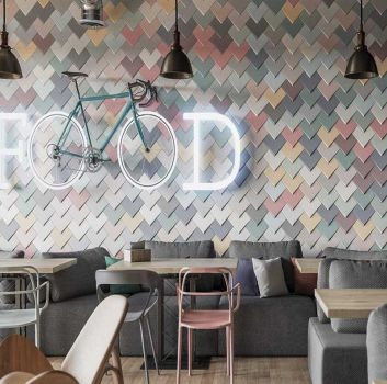 Multikolorowa restauracja z drewnianymi stolikami, szarymi siedziskami oraz metalowym regałem