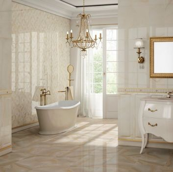 Marmurowa łazienka z wanną wolnostojącą nad którą wisi kryształowy żyrandol oraz białą szafką z wbudowaną umywalką