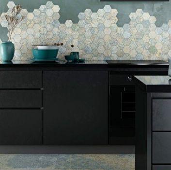 Niebieska kuchnia z czarnymi meblami, kwiatkiem oraz niebieskimi dodatkami