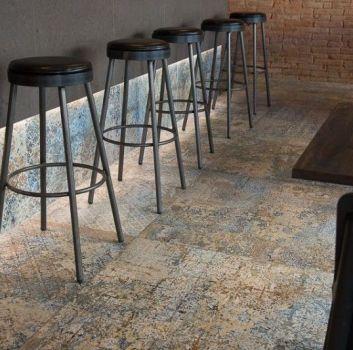Grafitowa restauracja z cegłą na ścianie, hokerami oraz drewnianymi stolikami z grafitowymi krzesłami