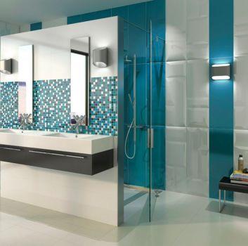 Biało-niebieska łazienka z prysznicem a przed nim na ścianie są dwie umywalki wbudowane w brązowe półki