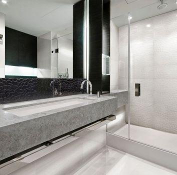 Szaro-biała łazienka z dużym prysznicem oraz umywalką wbudowaną w szarą płytę imitującą marmur