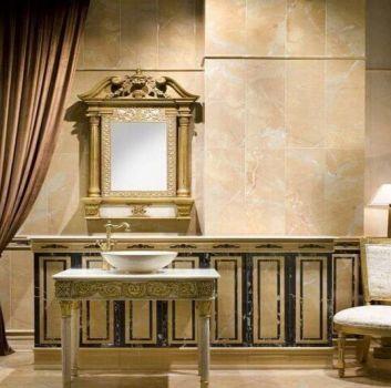 Beżowa łazienka ze wzorzystym stolikiem na którym znajduje się nablatowa umywalka a nad nią złote lustro