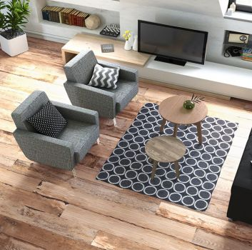 Biały salon z grafitowym kompletem wypoczynkowym, dużą ilością białych półek oraz biało-drewnianym blatem na telewizor