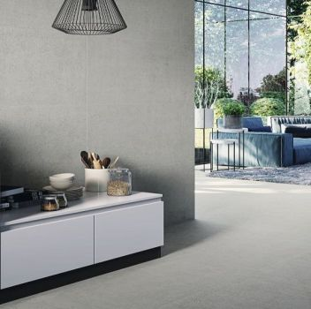 Szara kuchnia z białymi meblami, białym stołem z czarnymi hokerami i czarnymi, dwoma lampami