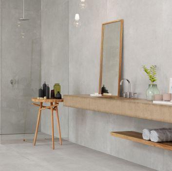 Szara łazienka z prysznicem, beżowym blatem z wbudowaną umywalką oraz drewnianymi dodatkami