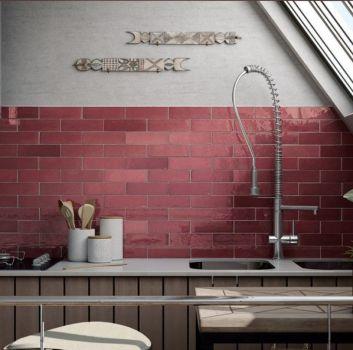Szaro-czerwona kuchnia z drewnianymi meblami, drewnianym stołem z białym hokerem oraz oknem dachowym