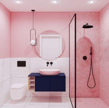 Różowo-biała łazienka z czarnym prysznicem, granatową szafką z umywalką nablatową oraz toaletą