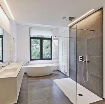 Biało-szara łazienka z wanną wolnostojącą, prysznicem oraz biała szafką z dwoma wbudowanymi umywalkami