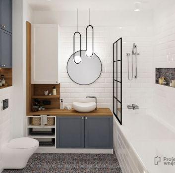 Biała łazienka z zabudowaną wanną, toaletą oraz niebieską szafką z umywalką nablatową