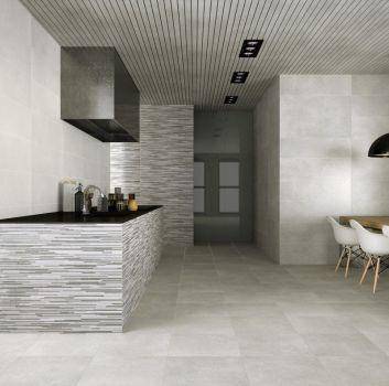 Biało-szara kuchnia z grafitowym blatem, drewnianym stołem z białymi krzesłami oraz nowoczesnymi lampami
