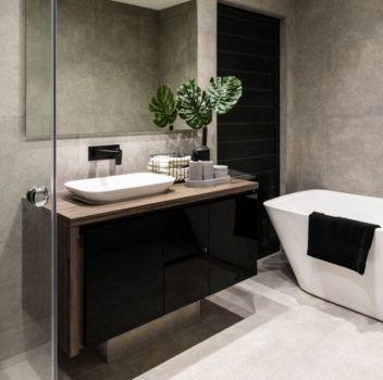 Biało-szara łazienka z wanną wolnostojącą, prysznicem oraz czarną szafką z umywalką nablatową