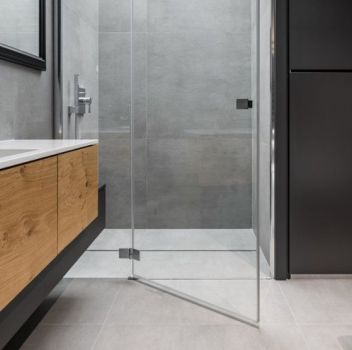 Szaro-biała łazienka z prysznicem, bidetem oraz drewnianą półką z wbudowaną umywalką