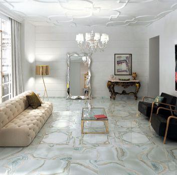 Jasny salon z oryginalną podłogą, pikowaną kanapą z dwoma fotelami i złotym stolikiem nad którym wisi kryształowy żyrandol