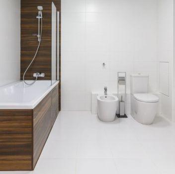 Biała łazienka z zabudowaną wanną, toaletą oraz białą szafką z umywalką nablatową