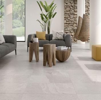 Biały salon z dużą ilością roślinności, szarym kompletem wypoczynkowym i trzema drewnianymi stolikami