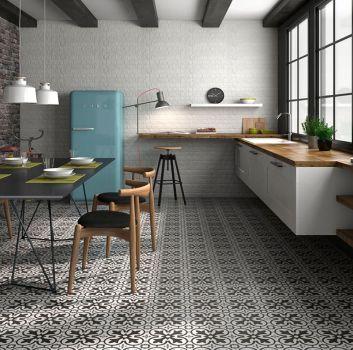 Biało-szara kuchnia z białymi meblami z drewnianymi blatami, niebieską lodówką oraz czarnym stołem z drewnianymi krzesłami