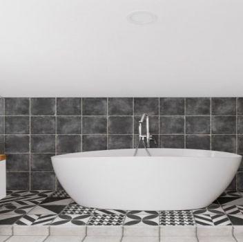 Biało-czarna łazienka z wanną wolnostojącą, toaletą oraz białą szafką z umywalką nablatową