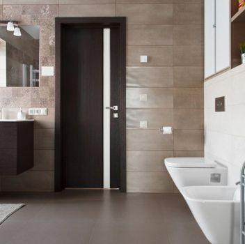 Brązowo-biała łazienka z toaletą, wanną oraz drewnianą szafką z wbudowaną umywalką