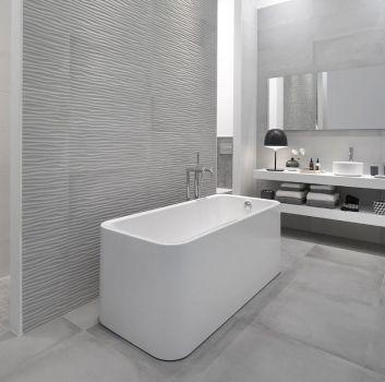 Biało-szara łazienka z wanną wolnostojącą, schowaną za ścianą toaletą oraz białym blatem, na którym stoją dwie umywalki nablatowe