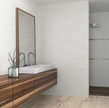 Biała łazienka z lustrzaną listwą w prysznicu, drewnianym blatem oraz umywalką nablatową