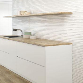 Biała kuchnia z drewnianymi blatami i białymi frontami oraz jadalnią z drewnianym stołem i białymi krzesłami
