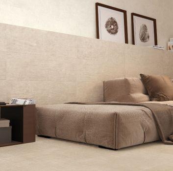 Beżowy salon z dużą, beżową kanapą, drewnianym stolikiem i półką zrobioną z płytek, która pełni funkcję szafki