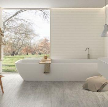Biało-szara łazienka z wanną wolnostojącą, połączoną z blatem umywalką oraz dużym oknem
