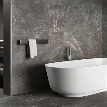Szara łazienka z wanną wolnostojącą, drewnianym blatem z dwoma umywalkami nablatowymi oraz drewnianą wnęką w ścianie