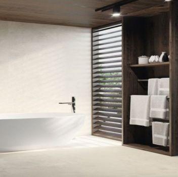 Beżowa łazienka z wanną wolnostojącą, drewnianymi otwartymi półkami oraz białym blatem z umywalką nablatową