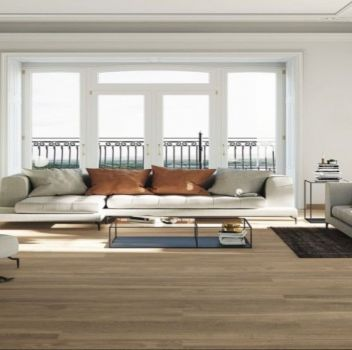 Biały salon z śmietankowym kompletem wypoczynkowym, otwartym przejściem do kuchni oraz dużym oknem