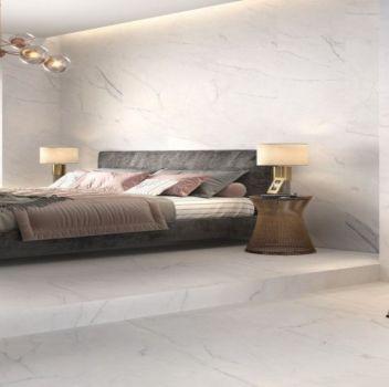 Biała sypialnia z wielkim łóżkiem, dwoma stolikami z lampkami nocnymi oraz toaletką