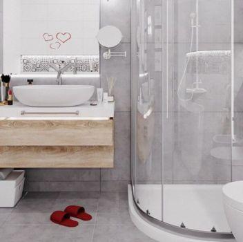 Szara łazienka z półokrągłym prysznicem, toaletą oraz drewnianymi szafkami z dwoma umywalkami nablatowymi