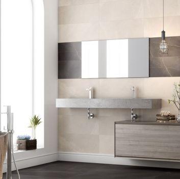 Beżowa łazienka z brązowym paskiem z płytek oraz lustrem, grafitową wanną wolnostojącą i dwoma zabudowanymi umywalkami
