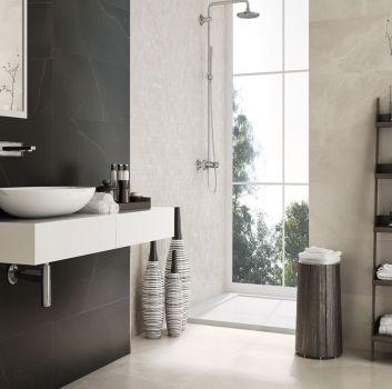 Beżowa łazienka z prysznicem przy oknie, drewnianą półką oraz białym blatem z umywalką nablatową