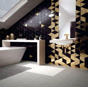 Czarno-złota łazienka z wanną wolnostojącą, białym blatem nad nią a obok umywalką ze złotym kranem