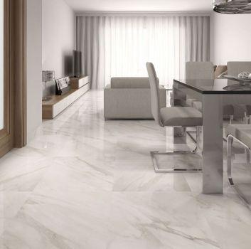 Biały salon z beżowym kompletem wypoczynkowym, drewnianą półką oraz jadalnią z szklanym stołem i beżowymi krzesłami
