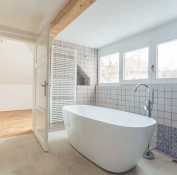 Biało-niebieska łazienka z wanną wolnostojącą, oknami oraz przejściem do kolejnego pomieszczenia