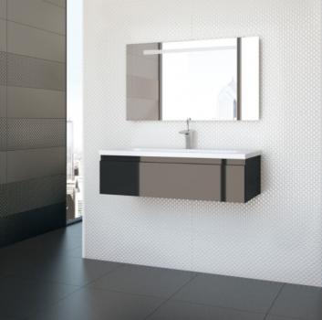 Szaro-biała łazienka z połyskującą szafką z zabudowaną umywalką, szarym stoliczkiem na kosmetyki a za ścianą jest otwarte przejście do sypialni