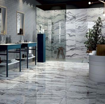 Szaro-biała łazienka z wanną wolnostojącą z drewnianym oparciem, prysznicem i dwoma granatowymi szafkami z dwoma wbudowanymi umywalkami