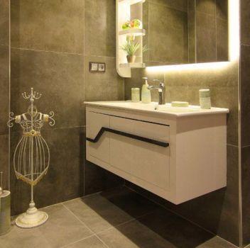 Ciemna łazienka z toaletą, białą szafką z wbudowaną umywalką a nad nią oświetlonym lustrem