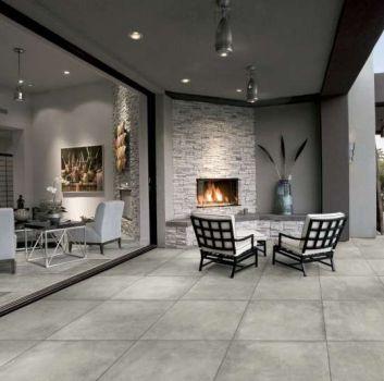 Szary salon z szarym kompletem wypoczynkowym, kominkiem i geometrycznym stolikiem